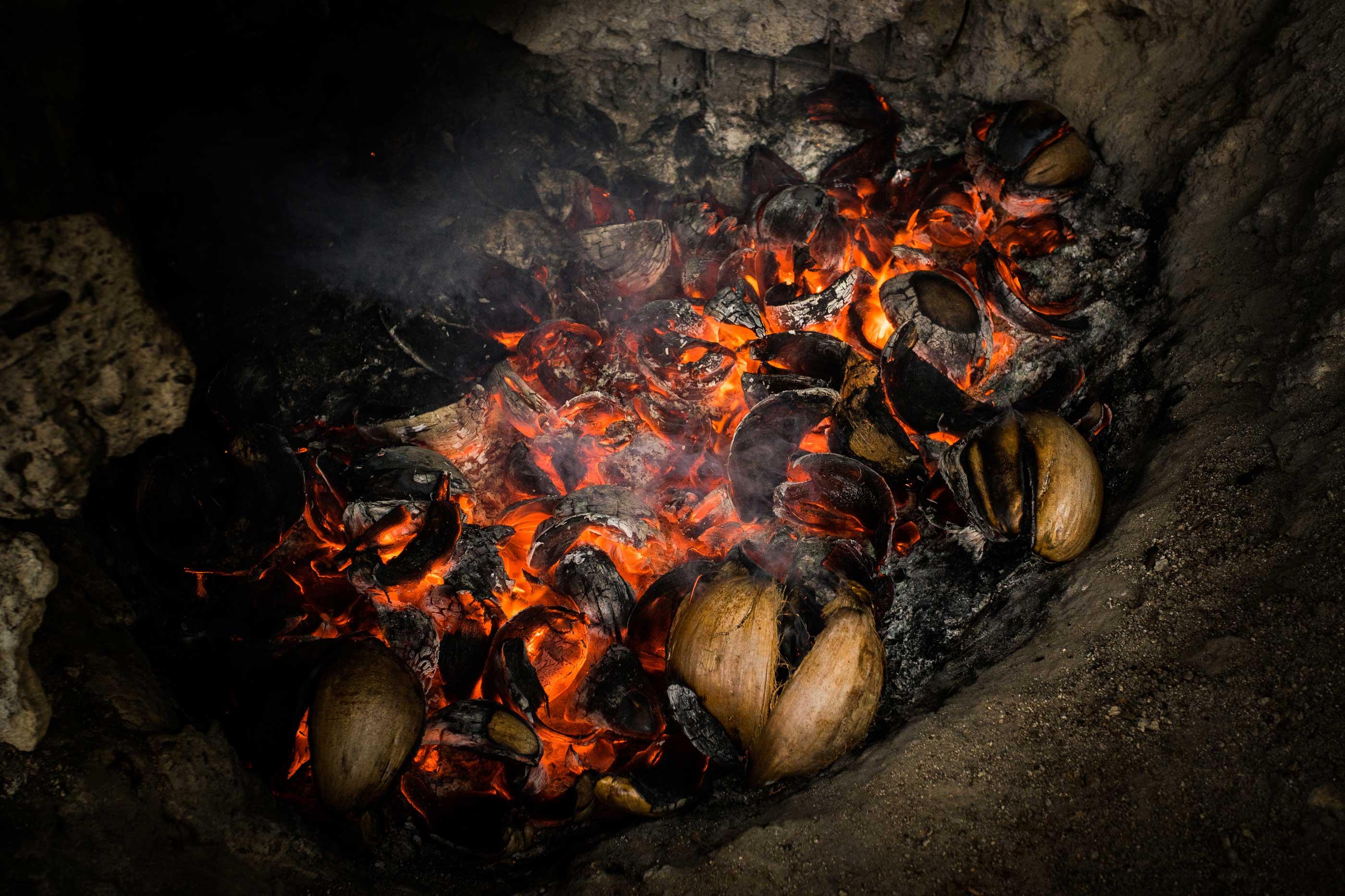 Kokosnussschalen werden für die Kokosbrikett Produktion verkohlt